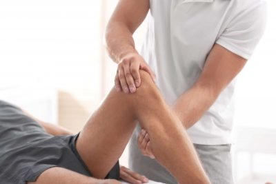 Patient having his knee examined by an osteopath