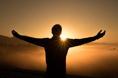 A man with his arms outstretched, facing into the sun