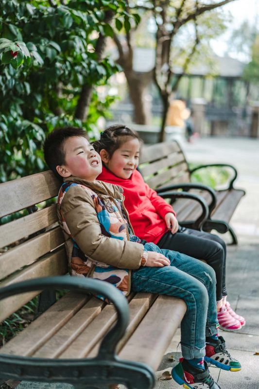 two children sitting on a park bench