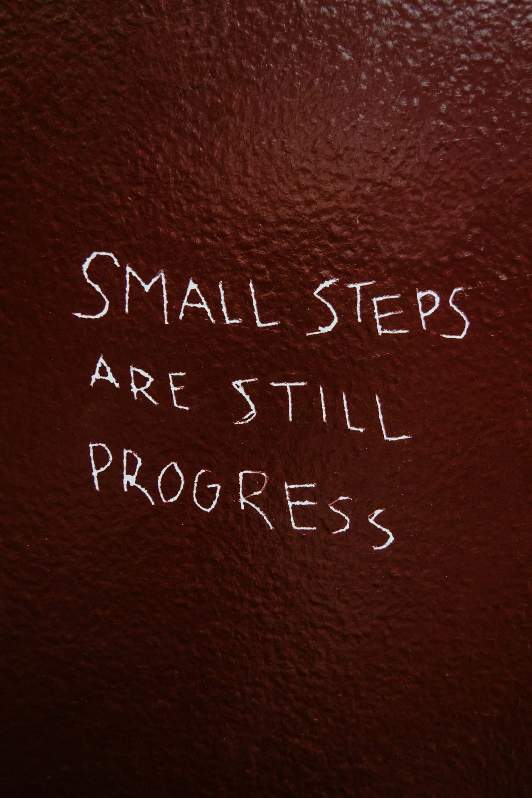 A sign saying 'Small Steps Are Still Progress'