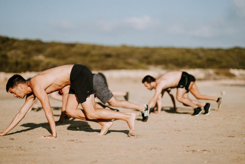 men on a beach racing on all-fours