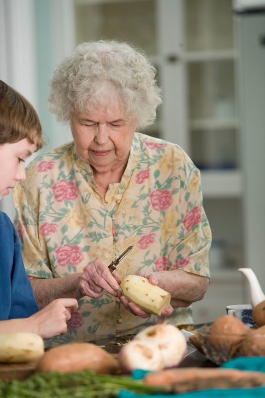 A picture of a grandmother cooking with her grandson